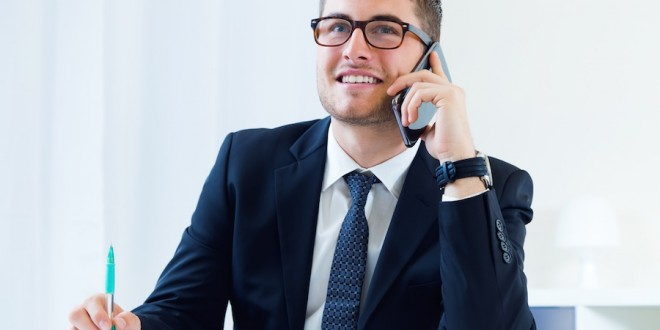 Portrait of young handsome man working in his office with mobile phone.